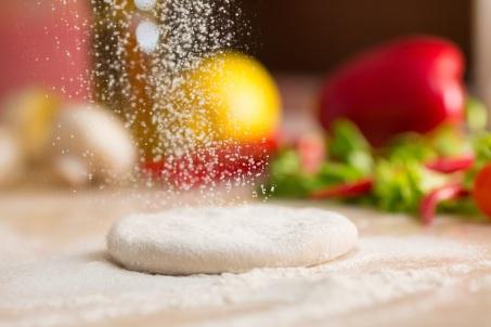 Dough for Italian pizza preparation. Falling flour.